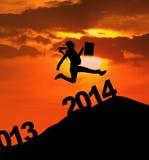 A silhueta da mulher de negócios salta sobre 2014 anos novos Fotos de Stock