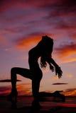 Silhueta da mulher em um joelho que ambas as mãos atrás dirigem para trás Fotografia de Stock