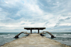 Silhueta da mulher em uma ponte abandonada velha do mar Imagem de Stock