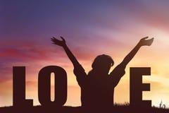 Silhueta da mulher feliz com texto do amor no por do sol foto de stock royalty free