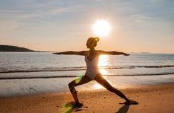 Silhueta da mulher da ioga na praia no nascer do sol A mulher está praticando a ioga no por do sol na costa de mar foto de stock royalty free