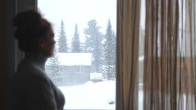 Silhueta da mulher madura borrada na observação envelhecida na janela em montanhas nevado bonitas Imagens de Stock