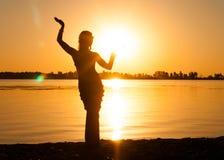 Silhueta da mulher magro que dança a dança tribal na praia imagens de stock
