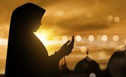 Silhueta da mulher muçulmana que reza com grânulos de oração Fotografia de Stock
