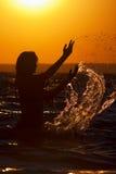 Silhueta da mulher no por do sol com um respingo Fotografia de Stock