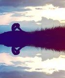 a silhueta da mulher preocupou-se na montanha no por do sol com água com referência a imagem de stock