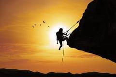 Silhueta da mulher que escala na rocha Foto de Stock