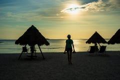 Silhueta da mulher que leva suas sapatas na praia do por do sol foto de stock royalty free