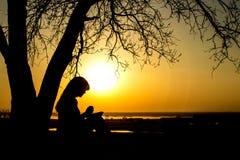 Silhueta da mulher que reza ao deus no witth da natureza a Bíblia no por do sol, no conceito da religião e na espiritualidade fotografia de stock royalty free