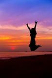 Silhueta da mulher que salta com mãos acima e que mostra EU TE AMO fotos de stock