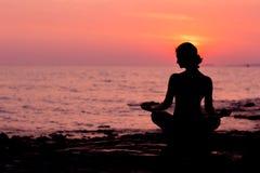 Silhueta da mulher que senta-se na posição dos lótus sobre o fundo do mar iluminado para trás Imagens de Stock