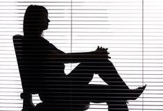 Silhueta da mulher que senta-se no escritório (cortinas) Fotografia de Stock Royalty Free
