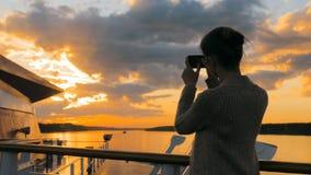 Silhueta da mulher que toma a foto do por do sol com o smartphone na plataforma do navio de cruzeiros Fotos de Stock Royalty Free