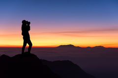 Silhueta da mulher que toma a fotografia na montanha superior Foto de Stock Royalty Free