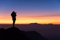 Silhueta da mulher que toma a fotografia na parte superior da montanha e Imagens de Stock