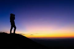 A silhueta da mulher que toma a fotografia na parte superior da montanha e aprecia o céu colorido Imagens de Stock Royalty Free