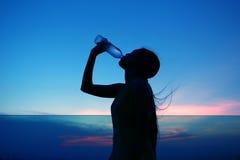A silhueta da mulher Rehydrate e refresca no por do sol Imagem de Stock Royalty Free