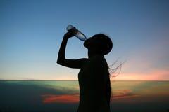 A silhueta da mulher Rehydrate e refresca no por do sol Imagem de Stock