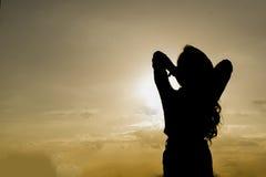 A silhueta da mulher reza com luz solar Fotos de Stock