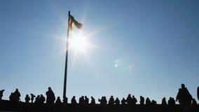 Silhueta da multidão dando uma volta e da bandeira alemão de voo contra o céu azul, Nuremberg filme