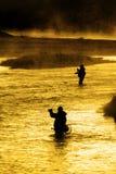 Silhueta da pesca Flyfishing do homem na luz solar dourada do rio Fotos de Stock