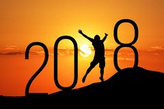Silhueta da pessoa que salta sobre 2018 no monte no por do sol Foto de Stock Royalty Free