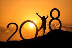 Silhueta da pessoa que salta sobre 2018 no monte no por do sol Imagem de Stock