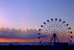 Silhueta da roda de Ferris com fundo do por do sol fotografia de stock