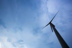 A silhueta da turbina eólica olha sobre acima a vista no fundo do céu azul fotografia de stock royalty free