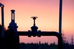 Silhueta da válvula de gás no fundo de um por do sol do outono imagens de stock royalty free
