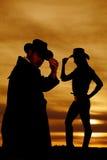 Silhueta da vaqueira do lado do toque do chapéu do olhar de um vaqueiro para baixo Foto de Stock Royalty Free