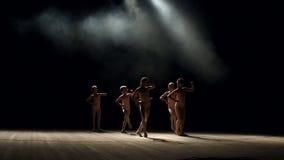 Silhueta das crianças pequenas que dançam na fase no fundo preto, movimento lento filme