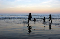 Silhueta das crianças que jogam na praia durante o por do sol Imagem de Stock