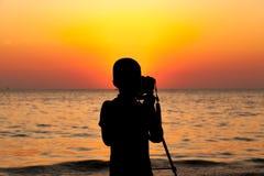 A silhueta das crianças que usam a câmera do dslr e o tripé tomam a foto do por do sol na praia , com luz bonita do por do sol Imagem de Stock
