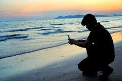 Silhueta das mãos do homem novo que guardam o telefone celular que tem o por do sol em férias de verão foto de stock royalty free