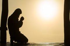 Silhueta das mãos humanas novas que rezam ao deus no nascer do sol, fundo do conceito de Christian Religion imagem de stock royalty free