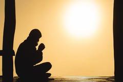 Silhueta das mãos humanas novas que rezam ao deus no nascer do sol, fundo do conceito de Christian Religion imagem de stock