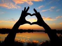 Silhueta das mãos na forma de um coração contra o contexto de um por do sol bonito imagens de stock