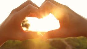 Silhueta das mãos na forma do coração com raios do sol de ajuste filme