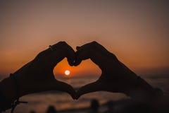 Silhueta das mãos que significam o amor no pôr do sol Imagem de Stock