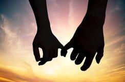 Silhueta das mãos tocantes no por do sol Conceito do amor imagem de stock