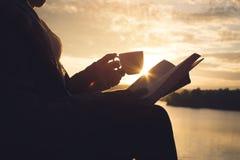 Silhueta das mulheres adultas felizes que leem um livro Foto de Stock Royalty Free