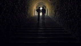 Silhueta das mulheres que partem em um túnel escuro vídeos de arquivo