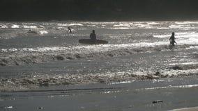 Silhueta das poucas pessoas que remam para fora em placas em ondas de oceano no por do sol Turistas que aprendem a surfar durante vídeos de arquivo