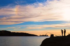 Silhueta de alguns povos que pescam no por do sol Fotografia de Stock Royalty Free