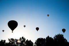 A silhueta de balões de ar decola foto de stock