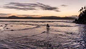 Silhueta de Bodyboarder do Seascape da aurora foto de stock