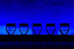 Silhueta de Cadeira de cinco diretores no estágio azul Fotografia de Stock Royalty Free