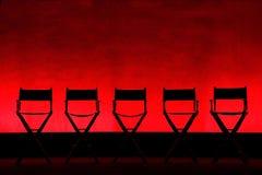 Silhueta de Cadeira de cinco diretores no estágio vermelho Fotografia de Stock