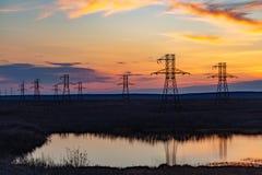 Silhueta de cargos de alta tensão no por do sol Norilsk imagem de stock